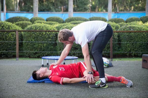 在上港巴西青训基地,体能教练吉列尔梅(右)在帮助球员孙亚军拉伸。孙亚军因骨裂无法上场训练。