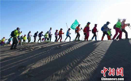 7月16日,来自广东、北京、福建等11个省市307名徒步爱好者在张掖国家沙漠体育公园内冒着38度的高温和地表温度近50度进行10公里徒步挑战沙漠戈壁比赛。图为徒步在沙漠戈壁中。 王将 摄