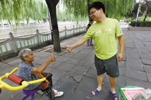 一位年轻人向老人竖起大拇指。