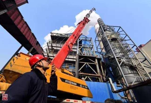 河北省沙河市一家玻璃生产企业的工作人员指挥吊车在脱硫塔上安装电除尘设备(2016年11月24日摄)。新华社记者 牟宇 摄