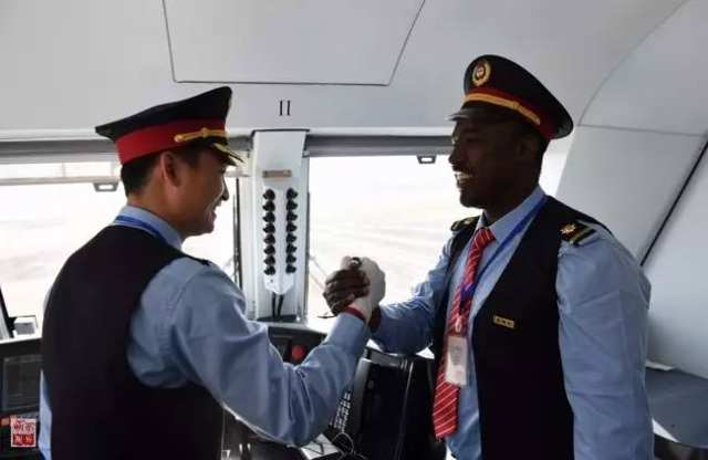 """在埃塞俄比亚首都亚的斯亚贝巴的拉布车站,中方司机刘继(左)和埃塞方司机盖图在亚的斯亚贝巴-吉布提铁路通车典礼前握手(2016年10月5日摄)。该项目是继坦赞铁路之后,中国在非洲修建的又一条跨国铁路,被誉为""""新时期的坦赞铁路""""。新华社记者李百顺摄"""
