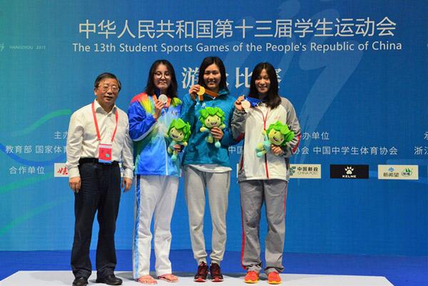 冠军刘湘(右二)与亚军傅园慧(左二)在学运会领奖台上。