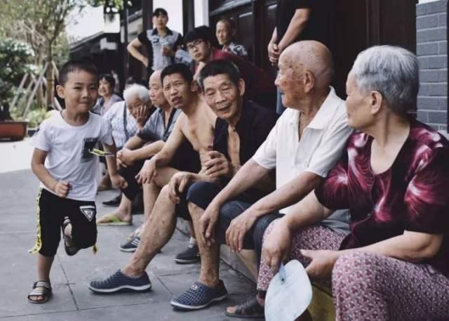 2017年7月13日,重庆奉节白帝城。一名男孩从坐在路沿上歇息的一排老人面前跑过。海军准将