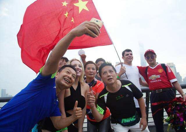 2017年10月1日,上海外滩。运动健身的市民和两位俄罗斯年轻人聚集在国旗下自拍,纪念难忘一刻。胥昆德