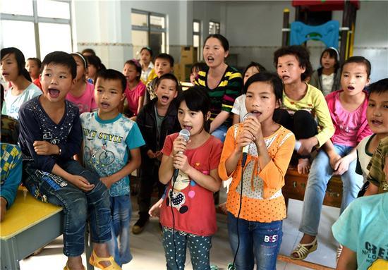 ; ; ; 2016年5月26日,在广西大化瑶族自治县板升乡弄勇小学,孩子们在电教室里唱歌。 新华社记者 黄孝邦 摄