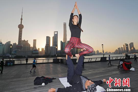 练习瑜伽的外籍人士在外滩滨江步道上不断摆出各种造型,成为了清晨黄浦江岸边一道独特的风景线。 殷立勤 摄