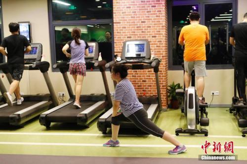 资料图:健身者正在做拉伸动作。中新社记者 殷立勤 摄