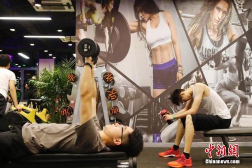 资料图:两名男生正在健身房健身。中新社记者 殷立勤 摄