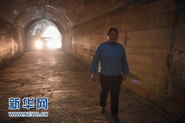 """在贵州罗甸县董架乡麻怀村,邓迎香进入她率领村民""""刨出来""""的人工隧道(2015年12月15日摄)。新华社记者 欧东衢"""