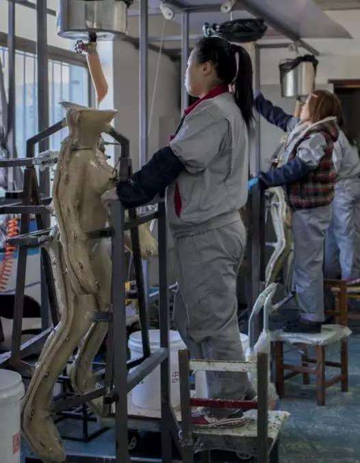技术工人正在将硅胶注入模具,注满硅胶后,需要等待六到八个小时,娃娃的身体才能凝固成型
